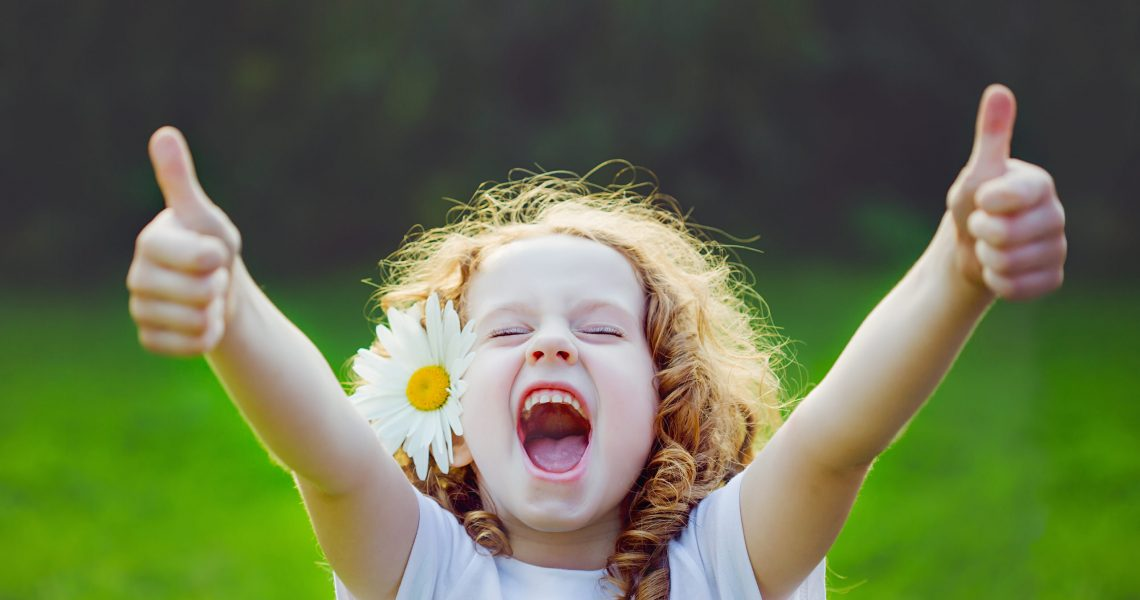 Laughing,Girl,With,Daisy,In,Her,Hairs,,Showing,Thumbs,Up.